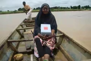 A health worker sails out for vaccination in a hard-to-reach community:  One of the heroes and heroines of Nigeria's Polio eradication success story