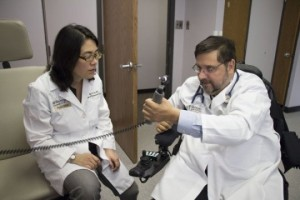 Washington University physician Michael Bavlsik, MD, shows surgeon Ida Fox, MD, how he can now grip an otoscope, which he uses in his practice. He is one of nine quadriplegic patients who regained some hand and arm movement after nerve-transfer surgery, a procedure pioneered at Washington University School of Medicine. Fox, an assistant professor of surgery, operated on Bavlsik. Courtesy: Science Daily