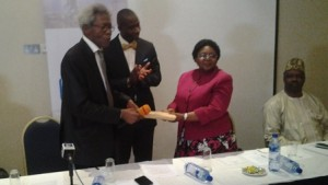Chairman, Nigeria Prize for Science Advisory Board, Prof. Alfred Susu (left) hands over the entries to the  Chairman, Panel of judges, Dr. Catherine Falade as NLNG General Manager, External Relations Dr. Kudo Eresia-Eke (centre) applauds. Sitting (right) is one of the judges, Prof. Sunday Atawodi.