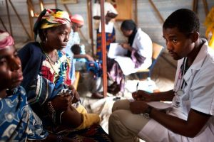 A doctor attends to a patient. A test is required to confirm malaria